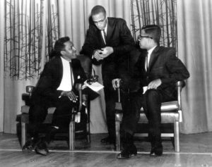 This is a October 30, 1961 photo of Bayard Rustin (seated left) and Malcolm X (standing) at their Howard University debate. Seated to the right is Michael Winston, the debate moderator. (Photo Credit: AP / John Duricka)